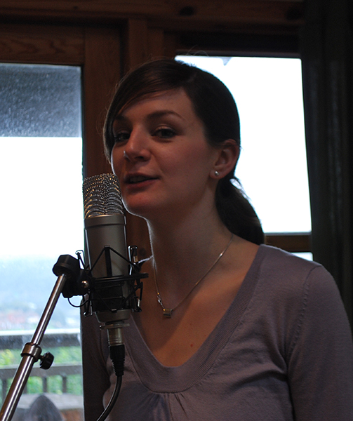 Laura singing into a microphone. - © 2010 Sam Carroll